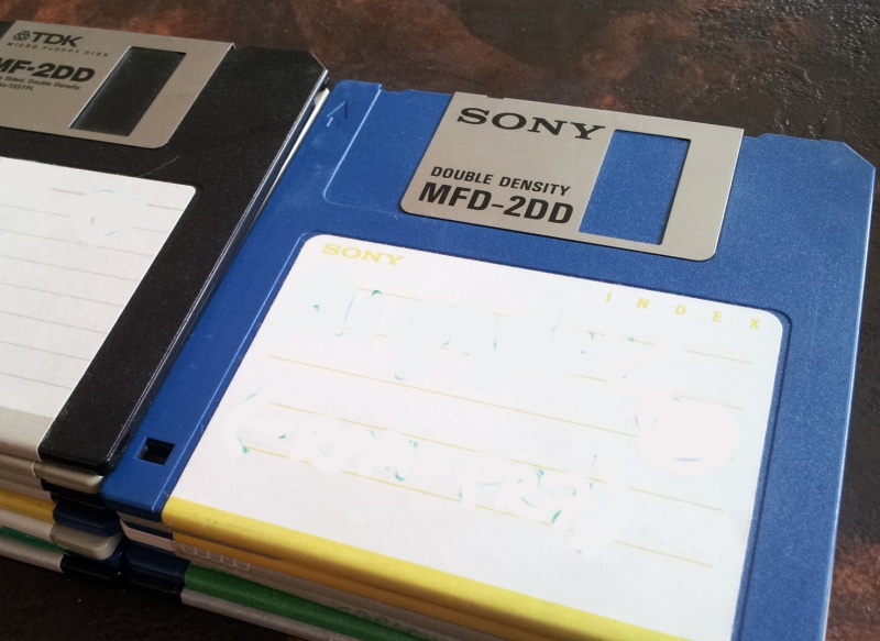 A stack of 3.5 inch floppy disks by Sony, TDK and Verbatim. There are 2 piles of disks with showing their aluminium dust covers and hard plastic protective cases. The disks are photographed side on.