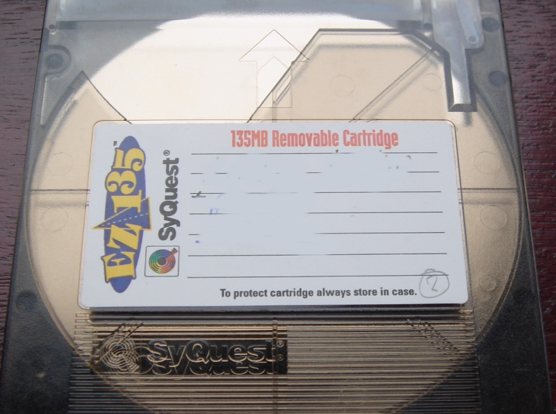A Syquest 135mb Ez-Drive disk is shown in the picture. The label indicates 135mb Removable Cartridge and the name Syquest is embossed on the cartridge.