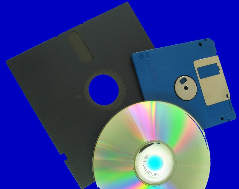 A CD, old 5.25 floppy disk and a modern 3.5 inch flopy disk together.