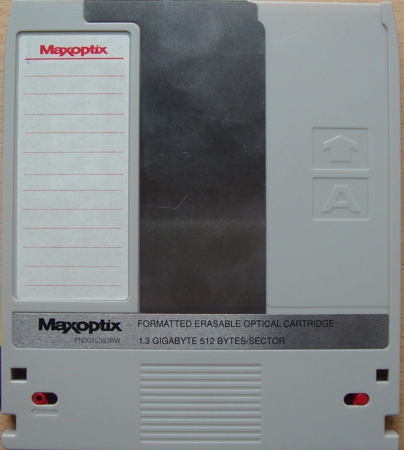 The front view of a Maxoptic Magneto Optical MO disk 1.3GB. The disk is grey colour with standard notches out of the side indicating ISO compliant formatting. The disk has it's read protect red tabs in thhe write protect position.