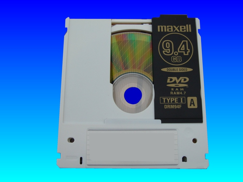 A Maxell 9.4GB Type I (Type 1) cartrdige case DVD-RAM disk with the slider door open exposing the DVD-RAM storage surface.