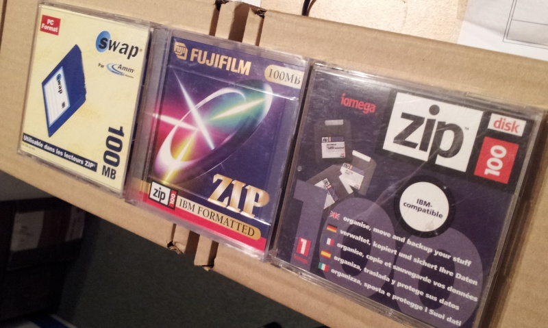 3 ZIP disks are shown, made by Iomega, FujiFilm and Swap. The disks are queued together ready to have their data read to a CD or DVD. In more recent years customers have asked for files to be saved to USB or have download links for getting the files returned to them.