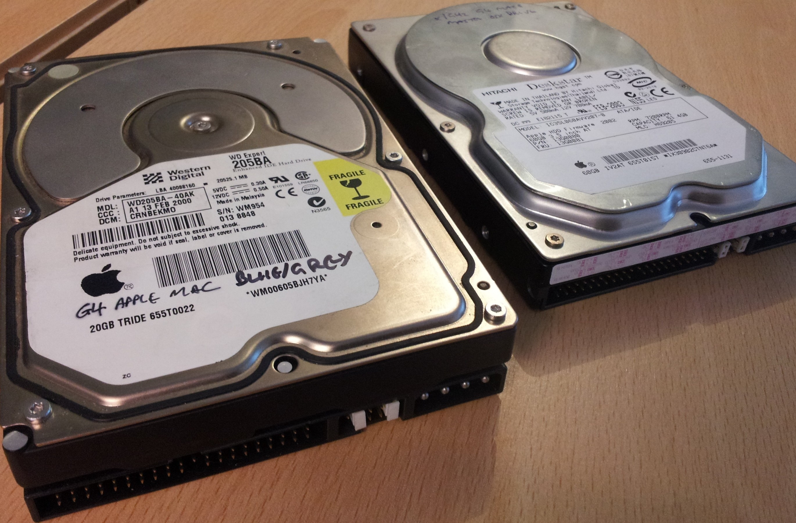 A pair of hard drives, one from an Apple G3, the other from a Mac G4, both with the Apple Logo on their label. One is a Western Digital Expert WD205BA 20GB and the is a 60GB Hitachi Deskstar IC35L060AVV207-0. These drives awaiting file transfer.