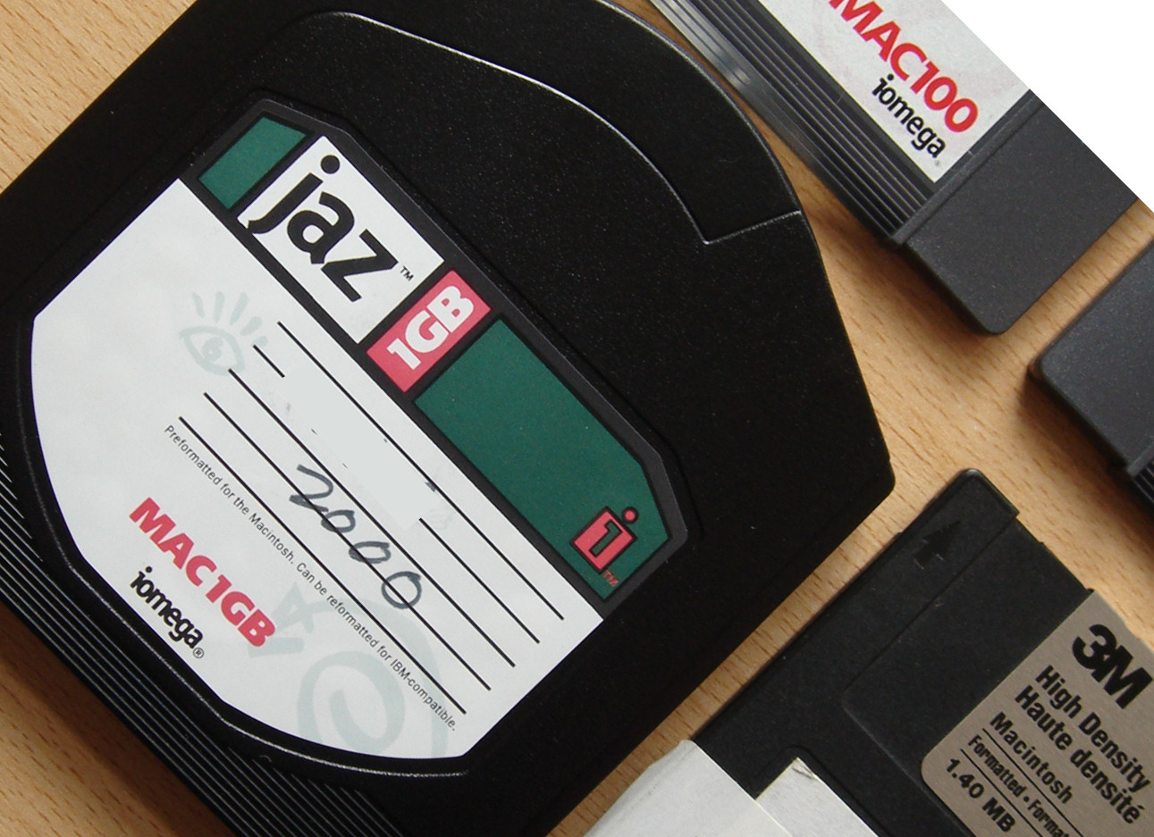 An Iomega Jaz disk pictured at a 45 degree angle with some other Jaz and floppy disks. The disks were ready for recovering data in our lab.