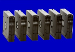 A series of DLT tapes shown lined up in a row. The tapes were used with Retrospect on an old Apple Mac under OS9 software. They had their data read and transferred to DVD and USB hard disk.