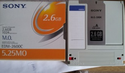 A Sony EDM-2600C MO disk 2.6gb with 1024bytes per sector, that is pictured along with its orange and white cardboard sleeve. The MOD was rewritable and formatted in HP Unix Workstation.