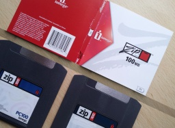 The photo shows 2x Zip 100 discs along with their title sleeve. The disks are made by Iomega and are 100mb capacity. The label indicates they are PC100.