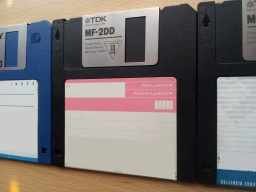 A row of 3 off floppy disks 3.5 inches awaiting Word file extraction. The disks are photographed at an angle with only part shown of disks 1 and 3.