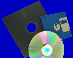 3.5 inch floppy disk from a Macintosh computer is pictured together with a CD denoting a transfer of data between the 2 media.
